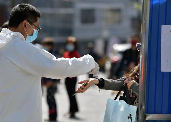 A staff member checks a resident's body temperature at the entrance of Chucai community in Wuchang District of Wuhan, central China's Hubei Province, April 15, 2020. (Xinhua/Li He)